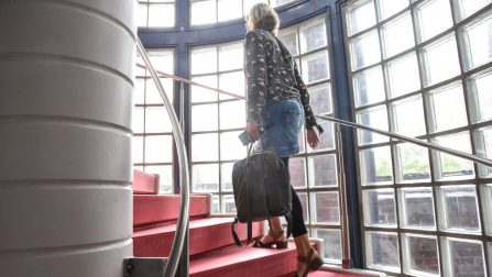 Ein Treppenhaus, ausgekleidet mit Glasbausteinen und roten Stufen. Eine Frau geht die Treppe hinauf.