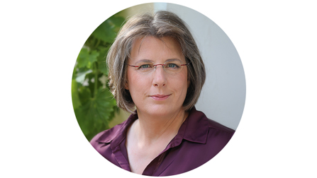Porträtfoto von Anke Lüken. Sie hat dunkelblonde kinnlange Haare, trägt eine Brille und eine lila Bluse.