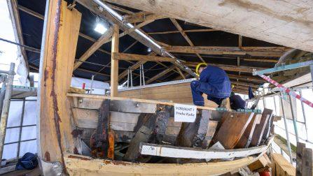 Ein Mann in Blaumann arbeitet am Holzgestell des Schiffes.