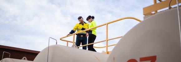 Eine Frau und ein Mann in gelben Warnwesten stehen auf einem Tank mit gelbem Geländer.