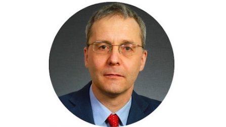 Porträtfoto von Prof. Dr. Martin Brussig. Er hat kurze Haare und trägt eine Brille, ein dunkelblaues Sakko, ein hellblaues Hemd und eine rote Krawatte.