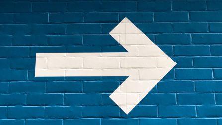 Ein weißer Pfeil, der nach rechts weist, auf einer blauen Backsteinwand.